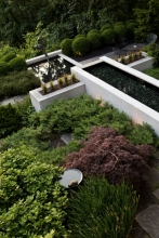 The strong rectilinear lines of the modernist concrete pool contrast with the soft textural plantings. Intimate seating areas provide spaces for dining and reflection.